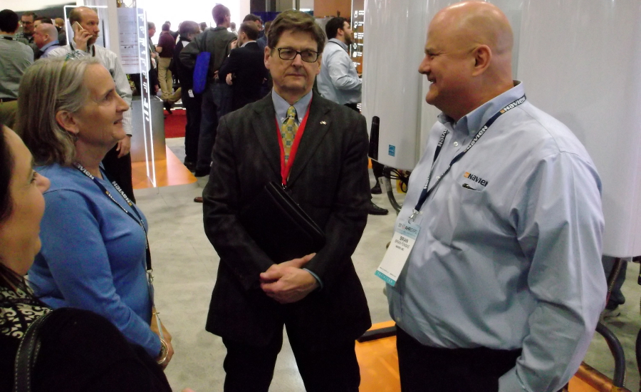 BNP Plumbing Group publisher Bob Miodonski, center, chats with Ann Woodard and Brian Fenske about Navien and its place in the water heater market