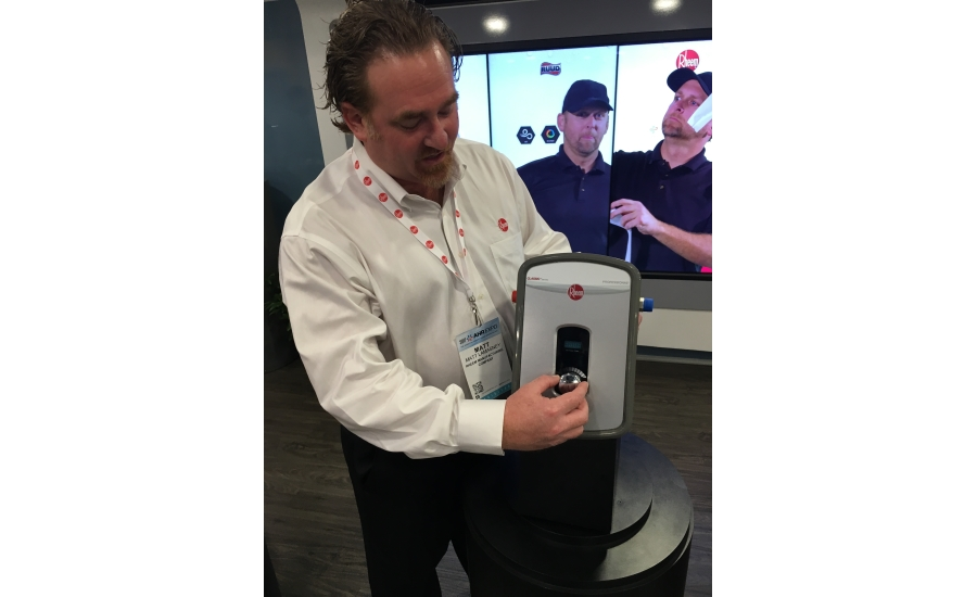 Rheem Mfg. Co.'s Matt Lamasney poses with one of the company's new individual tankless water heaters at the 2017 AHR Expo in Las Vegas