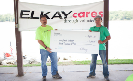 Ted Hamilton of Elkay (left) presents a check to Living Lands & Waters founder Chad Pregracke (right) at the companyâ??s recent river cleanup.