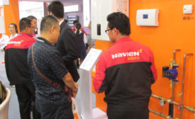 A Navien employee discusses the company�¢??s commercial condensing boiler with a booth visitor
