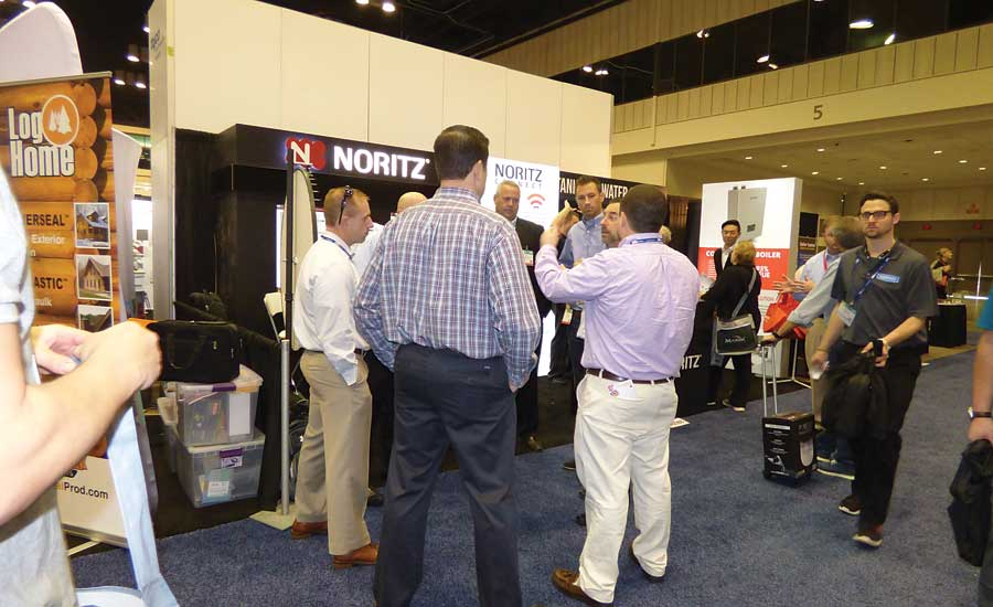 A group gathers around the Noritz booth at the NAHB Builders' Show side of the co-located event